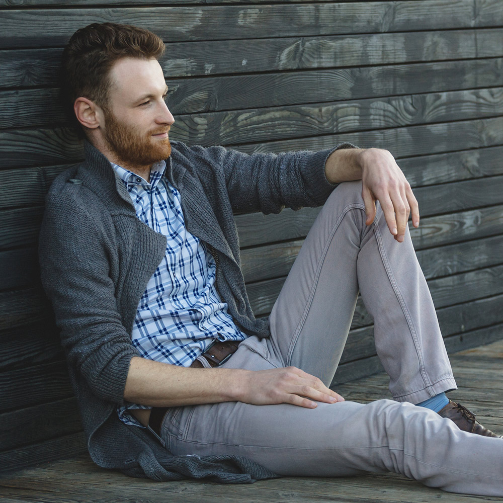 handsome-young-man-sitting-on-the-wooden-floor-WS